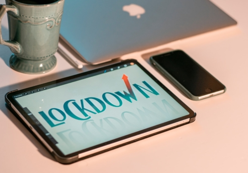 picture of a tablet showing the word lockdown. A mug is on the table next to it.