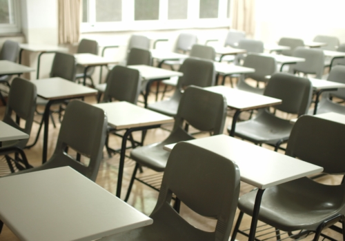 Picture of an empty school classroom with tables and chairs